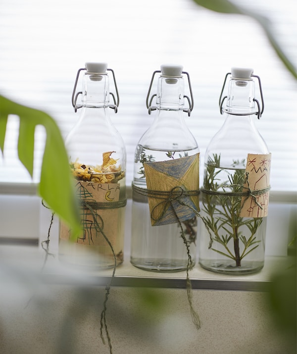Glass bottles full of liquid and herbs with handmade labels.