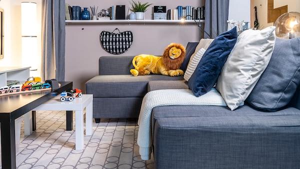 Sala com sofá de 3 lugares e chaise longue em cinzento com amofadas de cores variadas e mesa multifuncional para apoio