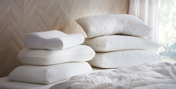 Several ergonomic pillows stacked on a bed.