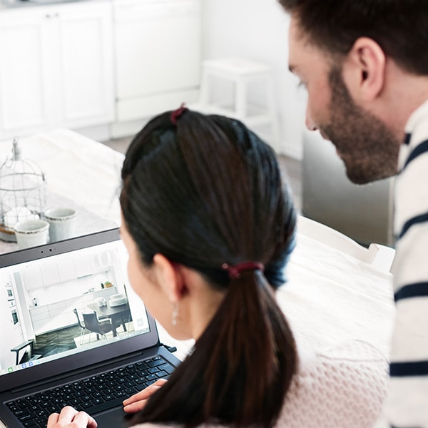 A young couple working on a laptop designing a kitchen from home.