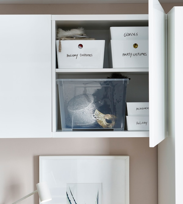 A white storage cabinet above a bed, opened to reveal labeled storage boxes within.