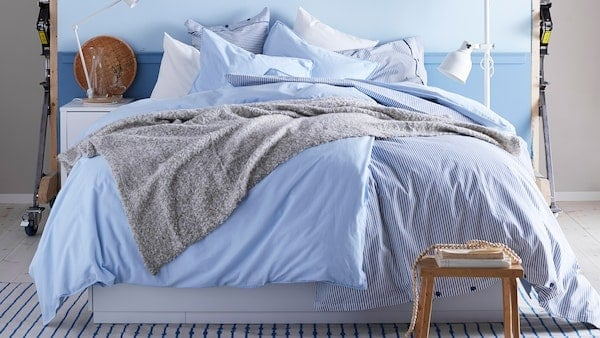 blue duvet with grey blanket on a white bed