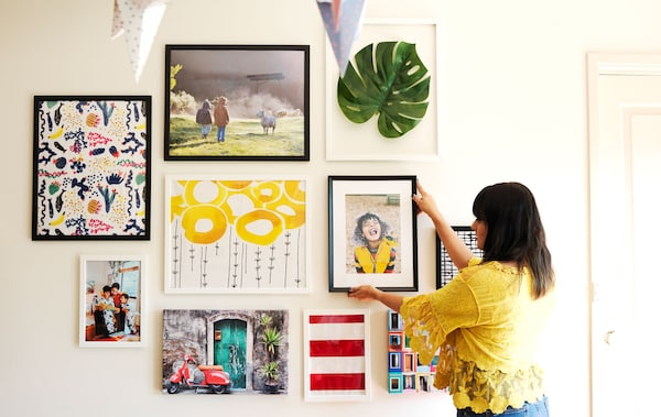 Abeer en train de placer une photo encadrée sur un mur d'exposition.