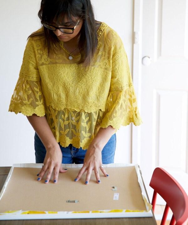 Abeer fissa il retro di una cornice - IKEA