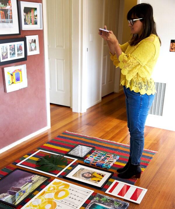 Abeer macht Fotos von gerahmten Bildern, die auf einem Teppich liegen.