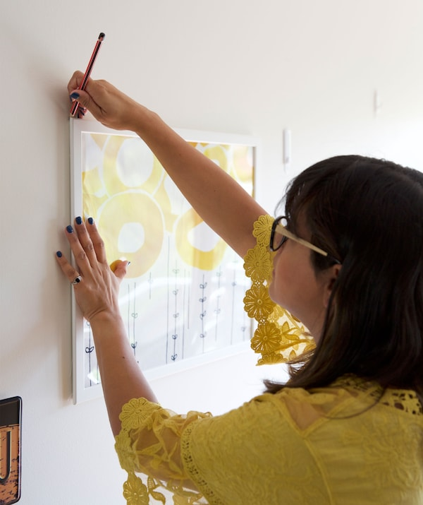 Abeer markiert die äusseren Ecken eines Bilderrahmens, u. a. mit STOCKHOLM Meterware in Weiss und Gelb.