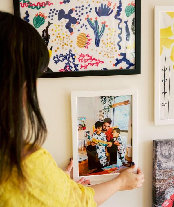 Abeer positioniert ein Familienfoto in einem FISKBO Rahmen an einer Galeriewand.