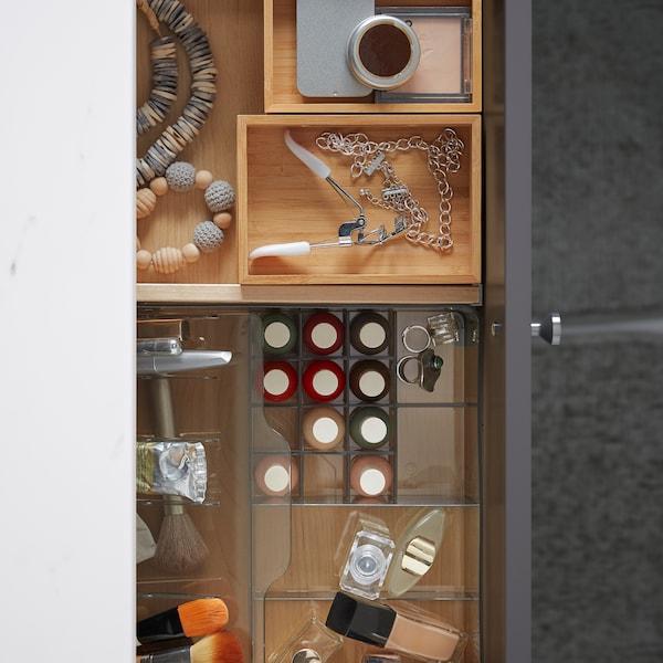 Åben badeværelsesskuffe med indretning af transparent plast med makeup og DRAGAN kasser af bambus med tilbehør.