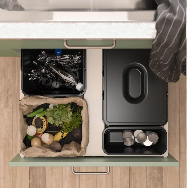 Åben køkkenskuffe med sorte affaldssorteringsspande set fra oven. Forskelligt affald er sorteret i dem.