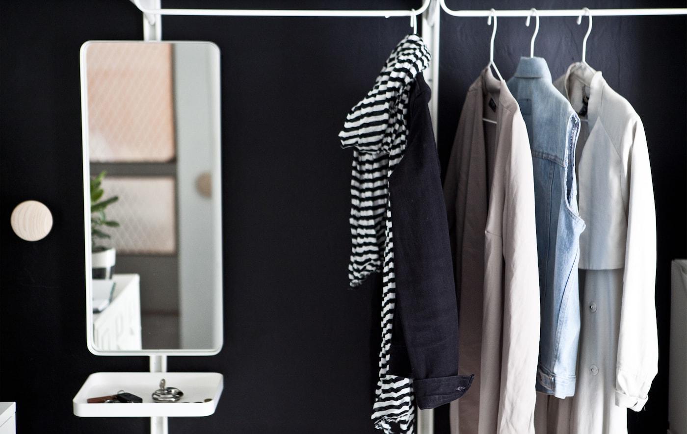 Abiti, giacche, cappotti e uno specchio con vassoio appesi a un binario sullo sfondo di una parete nera - IKEAd a mirror with a small tray hanging on a rail against a black wall.