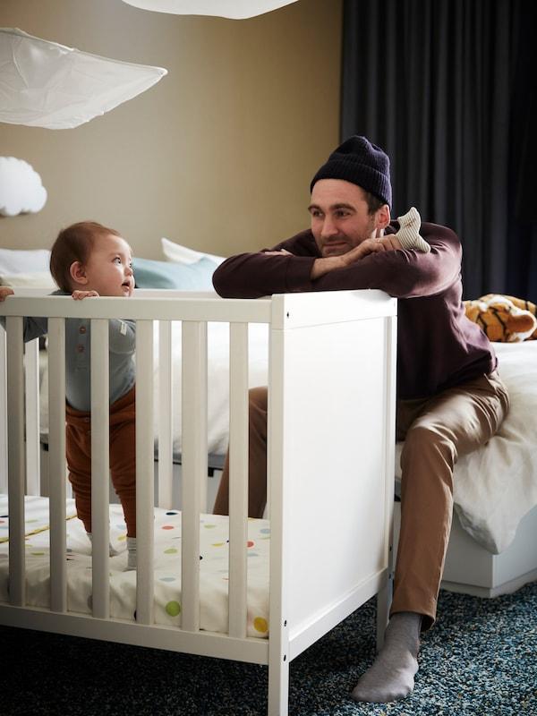 아기와 놀이 중인 아빠, 작고 부드러운 봉제인형, 화이트 SUNDVIK 순드비크 유아용 침대에서 난간을 붙잡고 서 있는 아기.