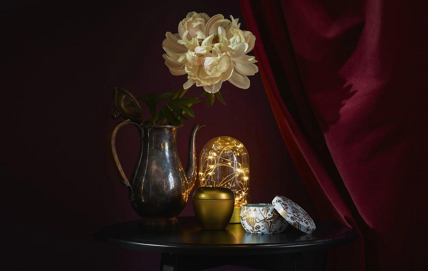 Accesorios dorados y luces en una mesa redonda contra un fondo rojo oscuro.