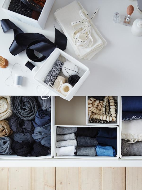 Accessoires de couture posés sur unecommode. Un tiroir ouvert révèle des vêtements bien rangés dans les boîtesSKUBB.