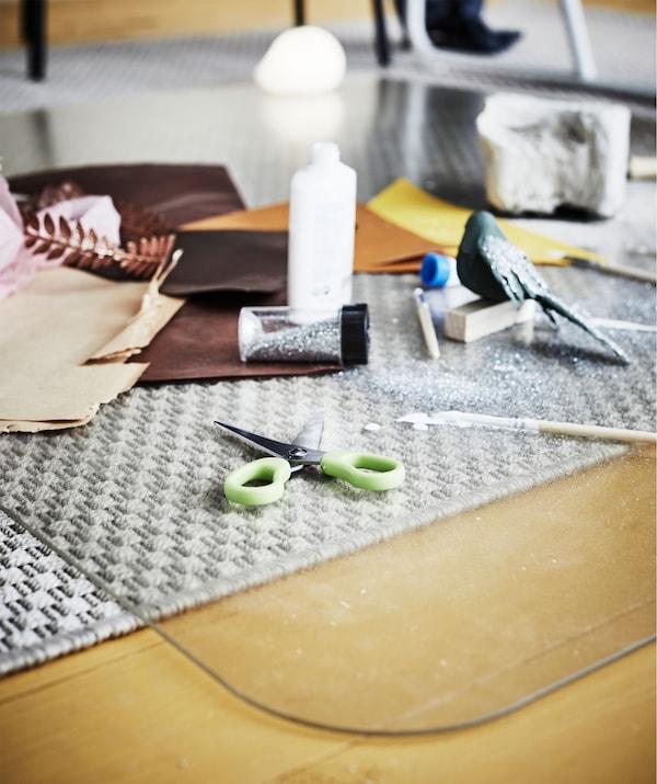 Accessoires de dessin, de peinture et de papier découpé répandus sur une protection pour sol qui met le tapis sous-jacent à l'abri du danger.