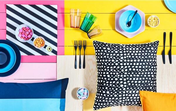 Accessoires de table, bols de friandises et coussins à motifs déposés sur une surface colorée.