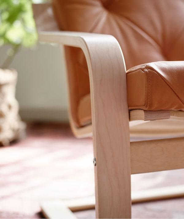 Accoudoir et cadre d'assise en contreplaqué d'un fauteuil, dans une pièce éclairée par le soleil, avec une plante à l'arrière-plan.