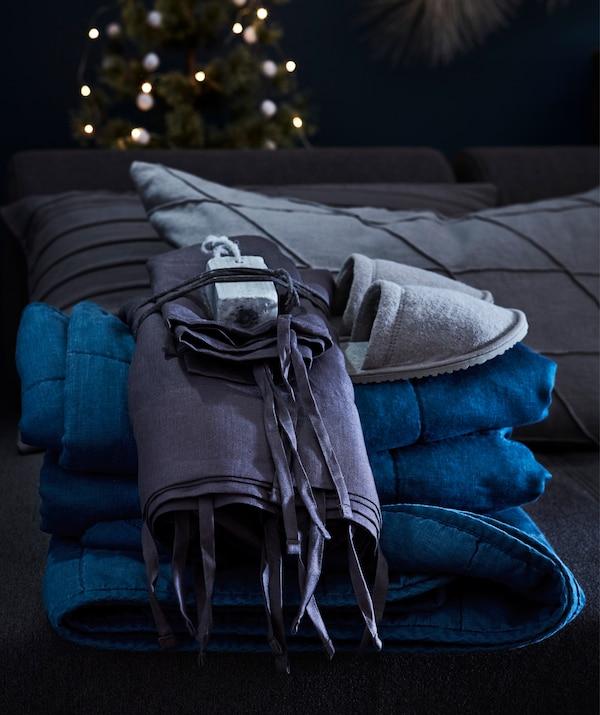 Accueille tes invités avec de jolies pantoufles, une housse de couette et une taie d'oreiller IKEA PUDERVIVA, et du linge frais.