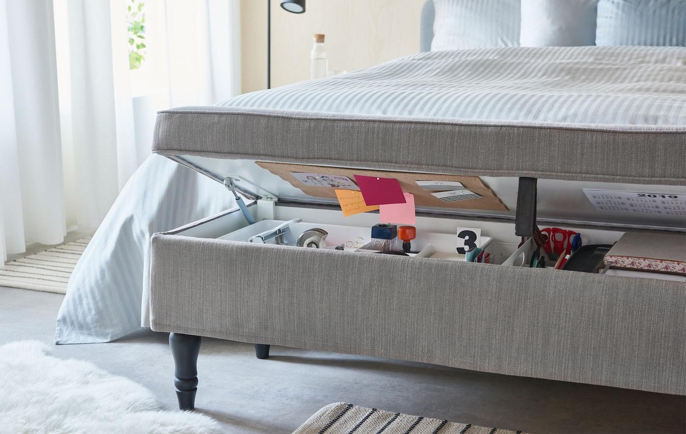 Acoperită cu material textil, o combinație de băncuță și soluție de depozitare ușor deschisă la piciorul unui pat, pe care sunt așezate obiectele caracteristice unui birou organizat acasă.
