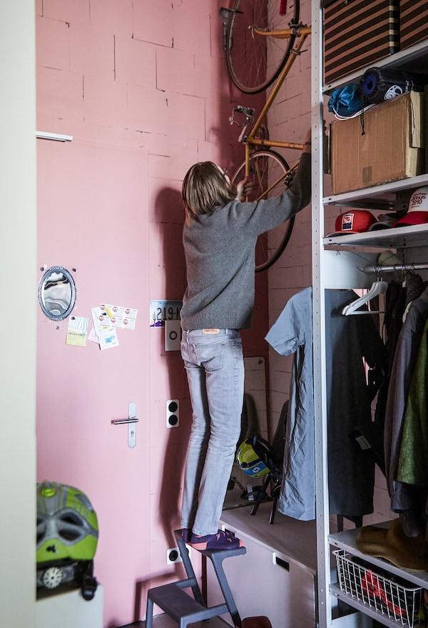 Adam en train d'accrocher son vélo à un mur rose.