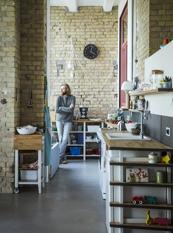 Adam standing in his kitchen with yellow brick walls and lots of open storage.