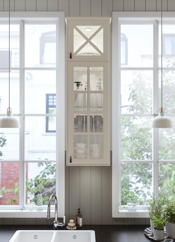 أدخل خزانة مطبخ بيضاء BODBYN من ايكيا في النافذة أو في مطبخك الصغير؛ تتيح لك أبواب العرض الزجاجية رؤية جميع الأواني الزجاجية.