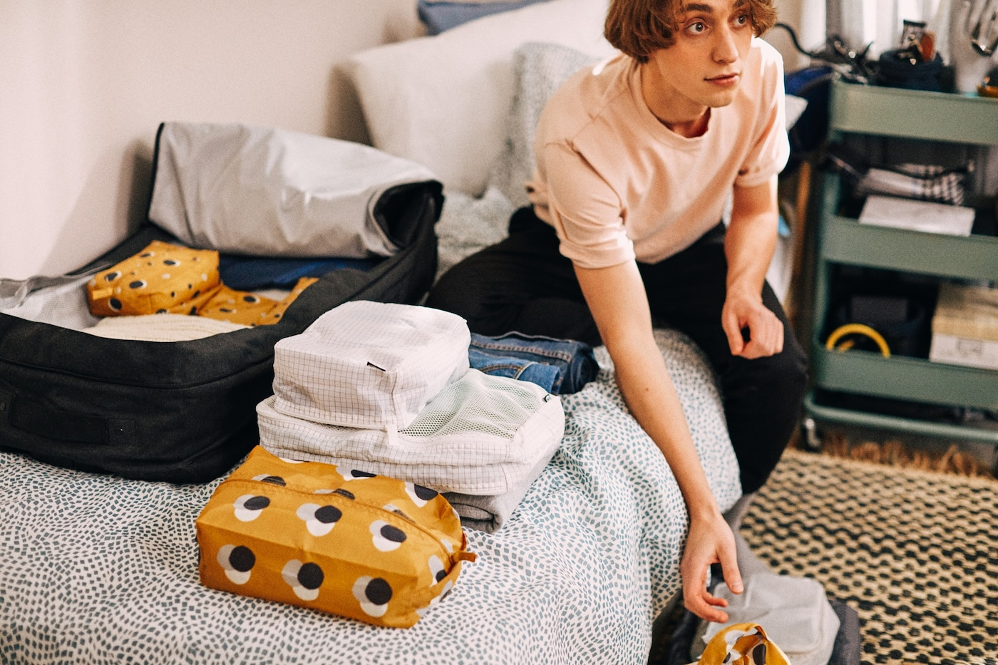 Adolescent assis sur un lit en train de faire sa valise.