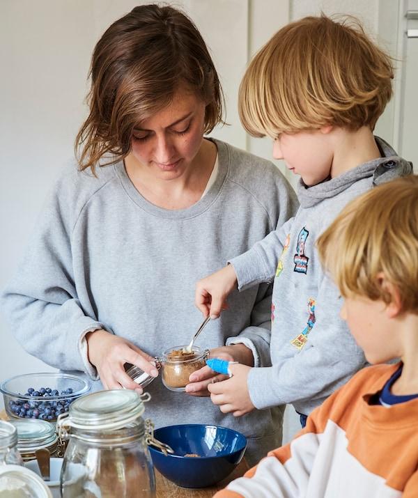 Äiti ja kaksi lasta tekevät yhdessä ruokaa keittiössä.