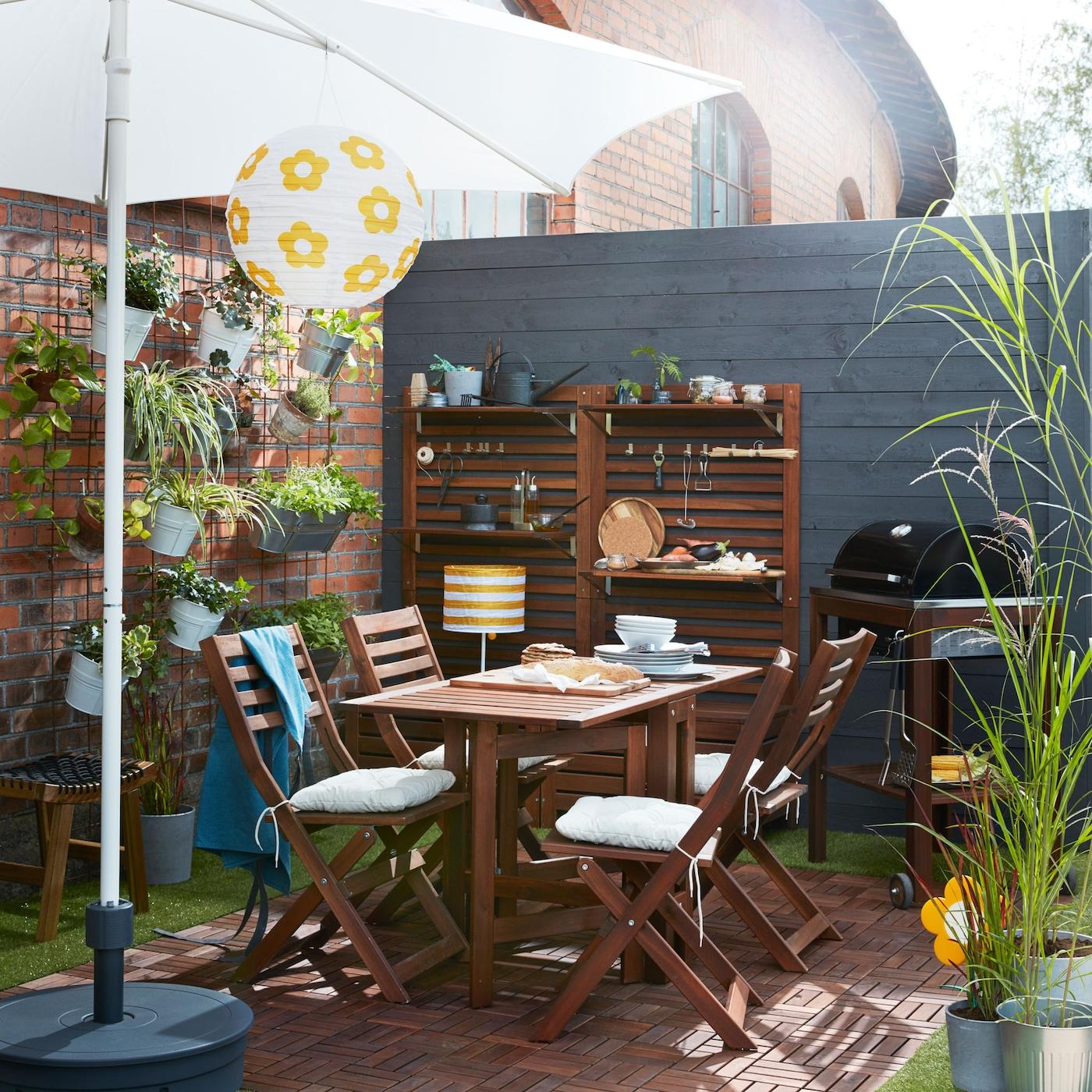 ÄPPLARÖ stoelen in donker gekleurd hout, uitschuifbare tafels en opbergeenheden in een moderne groene oase met planten uit het IKEA-assortiment.