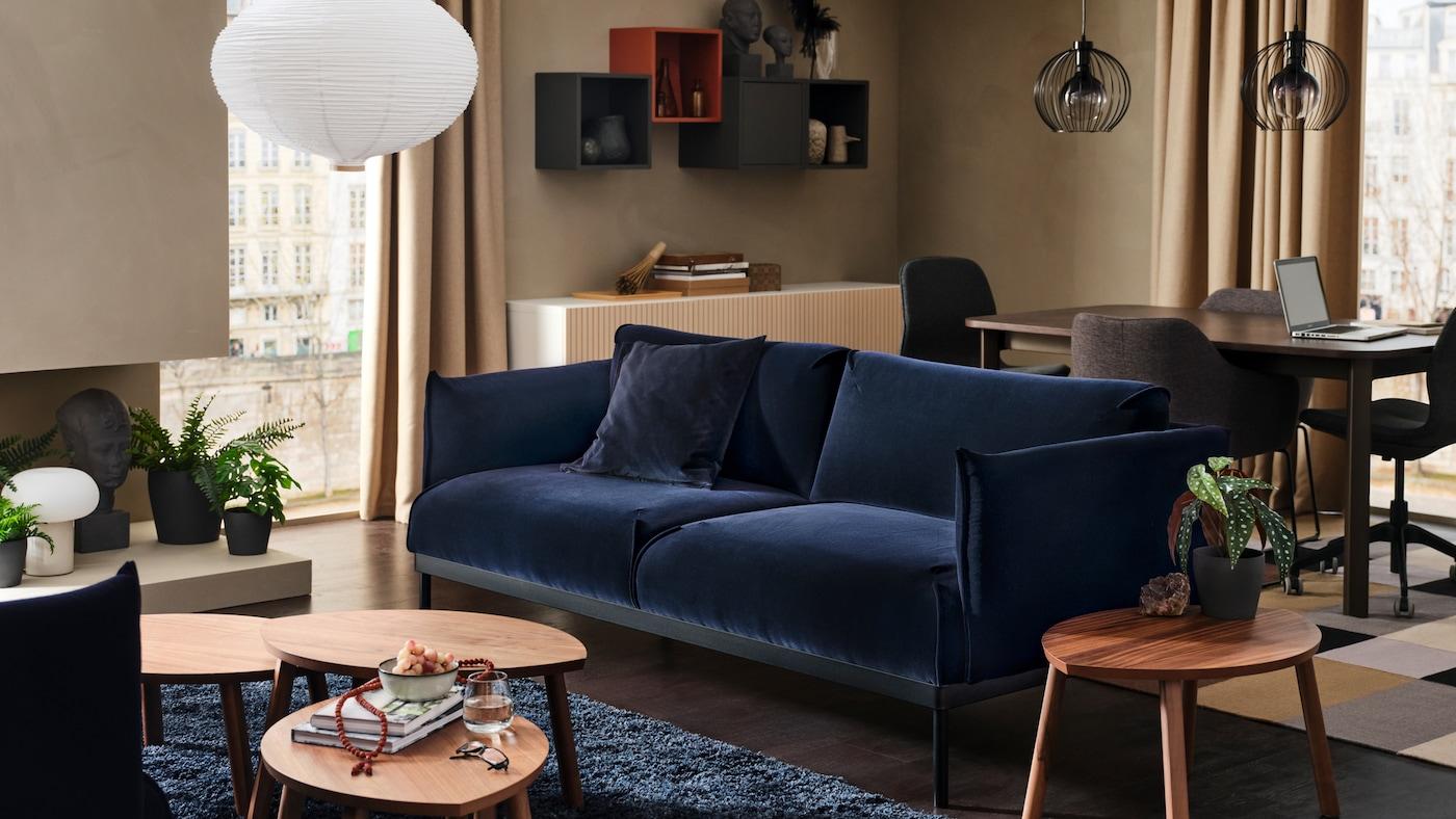 블루 장모 러그 위 ÄPPLARYD 에플라뤼드 소파 앞에 세 개의 커피테이블이 있고 소파 뒤에 식탁과 의자가 있는 모습.