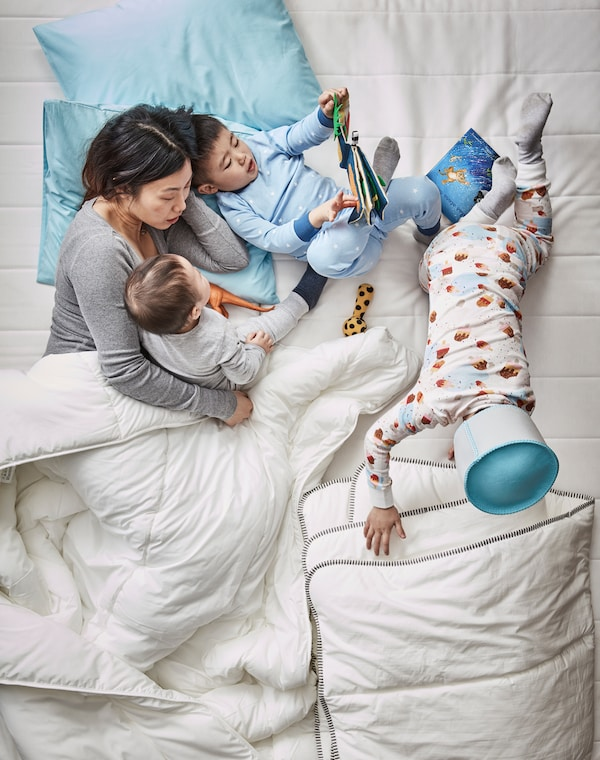 Aerial view of a mother and three children in bed reading DJUNGELSKOG  picture book and playing about under duvets.