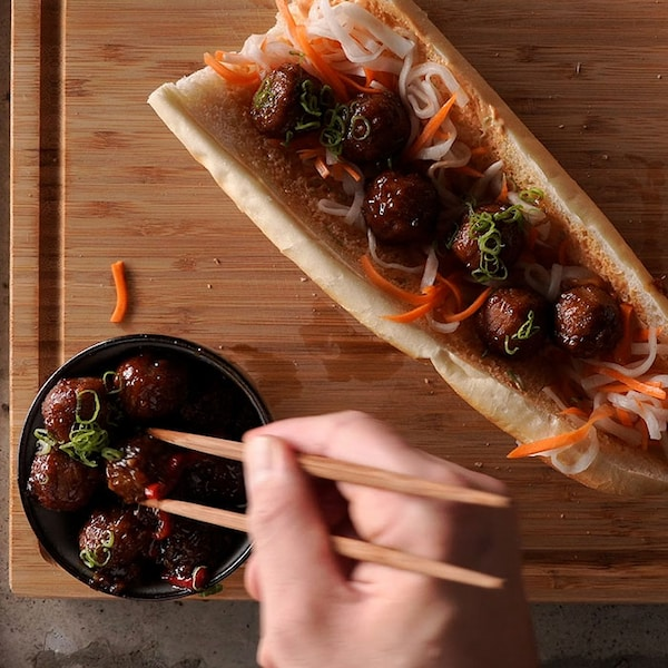 Aerial view of a vegetarian bahn mi sandwich made with IKEA plant balls, with a hand holding chopsticks and reaching into a bowl of extra plant balls.
