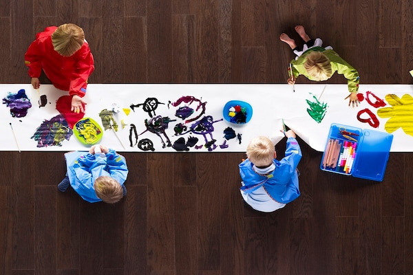 aerial view of kids painting on a long roll of paper