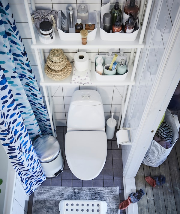 Aerial view of toiletries on storage shelves above a toilet, in a white tiled bathroom.
