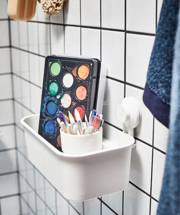 Æske med vandfarver og et krus fyldt med pensler i en kurv med sugekopper på en flisevæg i et badeværelse. Ved siden af hænger brusetilbehør.
