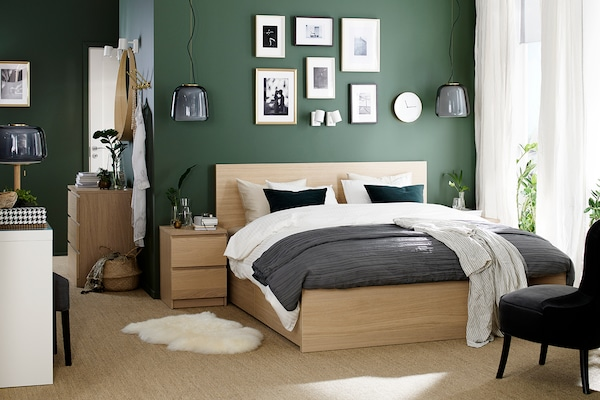 Beige MALM bed against a green wall.