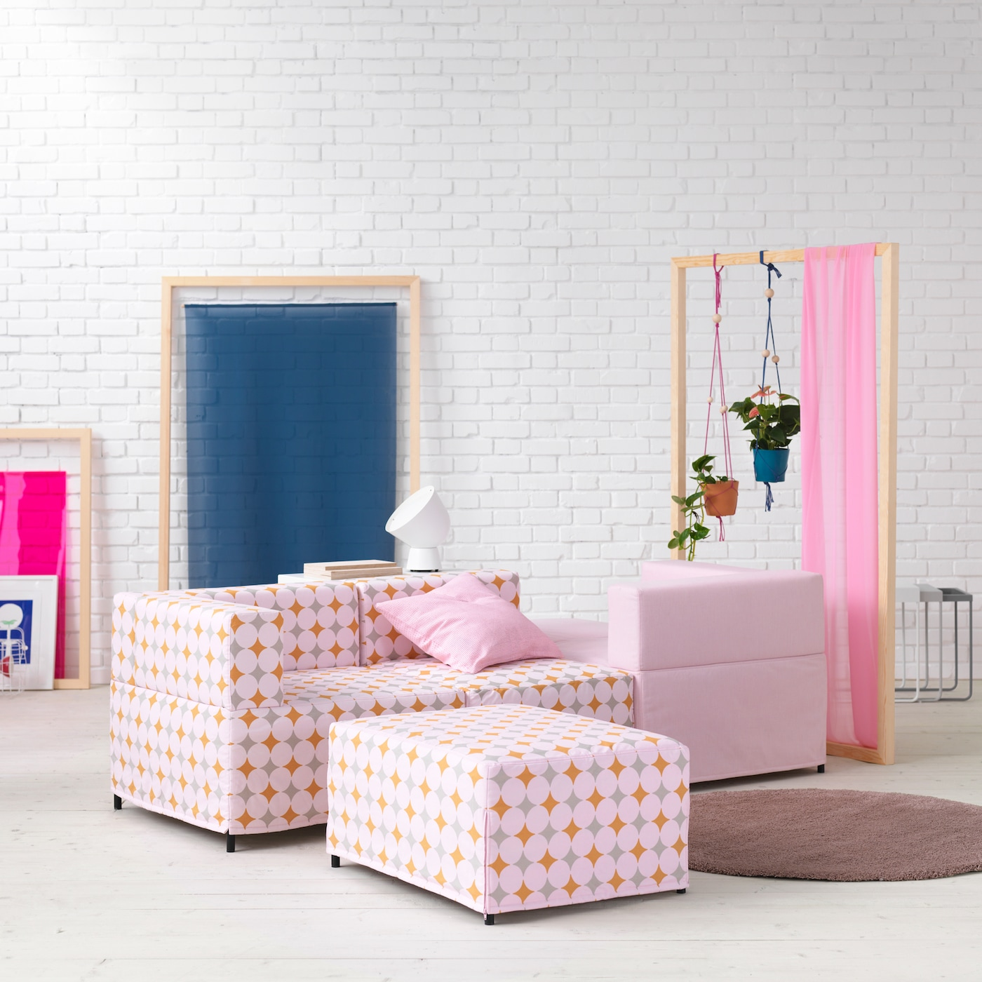 Affordable KUNGSHAMN modular sofa built in a creative way, with pink and pastel patterned covers, with a round rug.