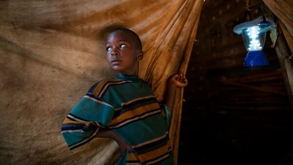 Afrikai fiú áll egy menekülttáborban.