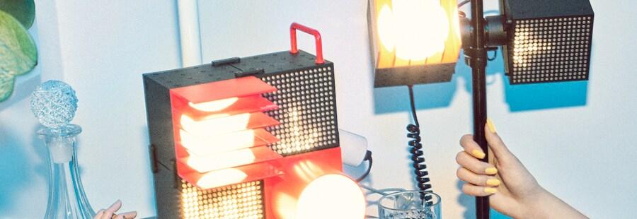 Afzonderlijke speakers en spots in zwart, rood en geel staan op elkaar gestapeld op een tafel in zwart en wit.