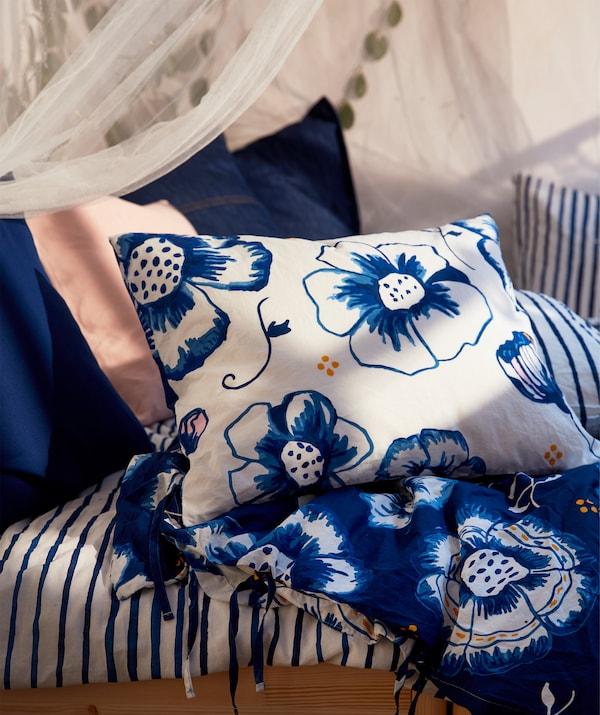 Ágy, ágyneművel, párnák és díszpárnák kék-fehér virágos mintával.