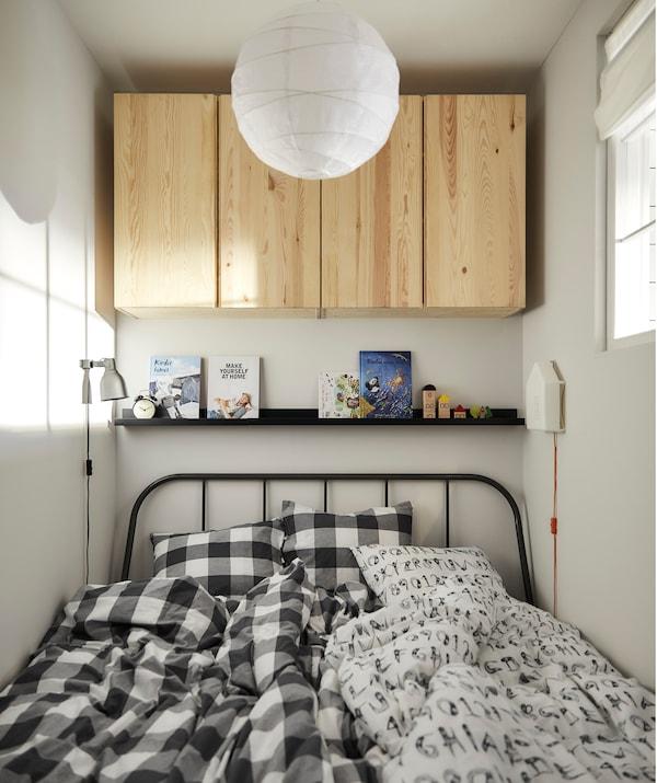 Ágy, két paplannal, könyvekkel és egy képtartóval, fa szekrények a falon.