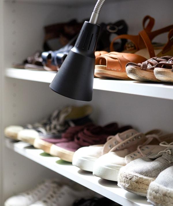 أحذية مصفوفة على رفوف مع مصباح عمل أسود.