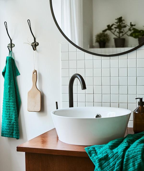 Ainutlaatuinen allaskaluste on tehty yhdistämällä moderni, pyöreä allas vanhaan työpöytään. Seinällä on valkoisia laattoja ja pyöreä, mustareunuksinen peili.