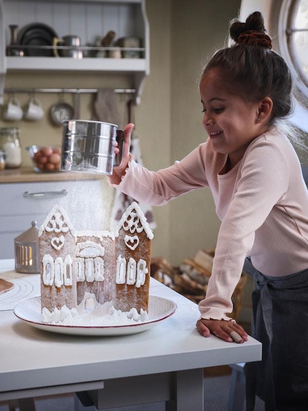 アイシングでデコレーションされたジンジャーブレッドハウスの上に、IDEALISK/イディアーリスク 粉ふるいで砂糖を吹雪のように振りかける少女。