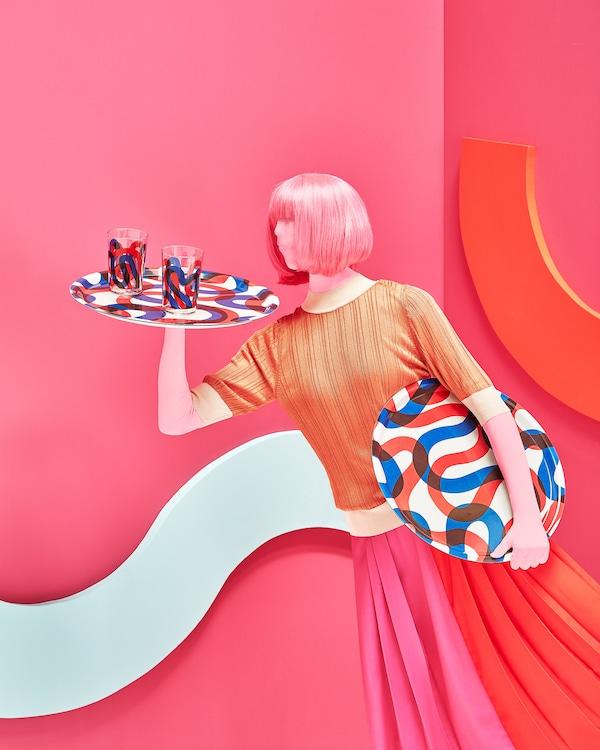 Ajoutez de la couleur à la table à l'aide du plateau circulaire FRAMKALLA de IKEA. Son motif tout en courbes propose de larges bandes rouges et bleues sur fond blanc. Des verres et autres articles coordonnés sont aussi offerts.