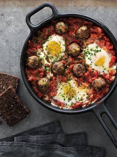 Albóndegas vexetais en salsa de tomate con ovos escalfados, servidas nunha tixola de ferro fundido, vistas dende arriba.