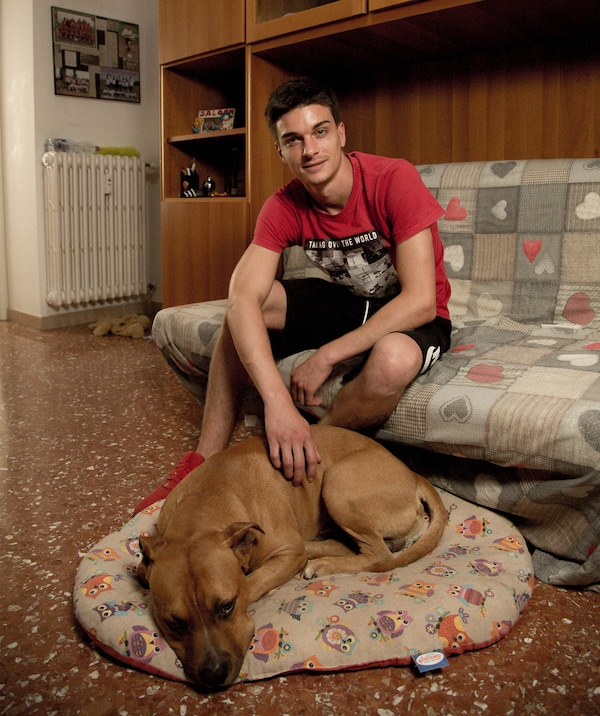 Alessandro sits on a sofa and a dog lies on a dog bed in front of him.