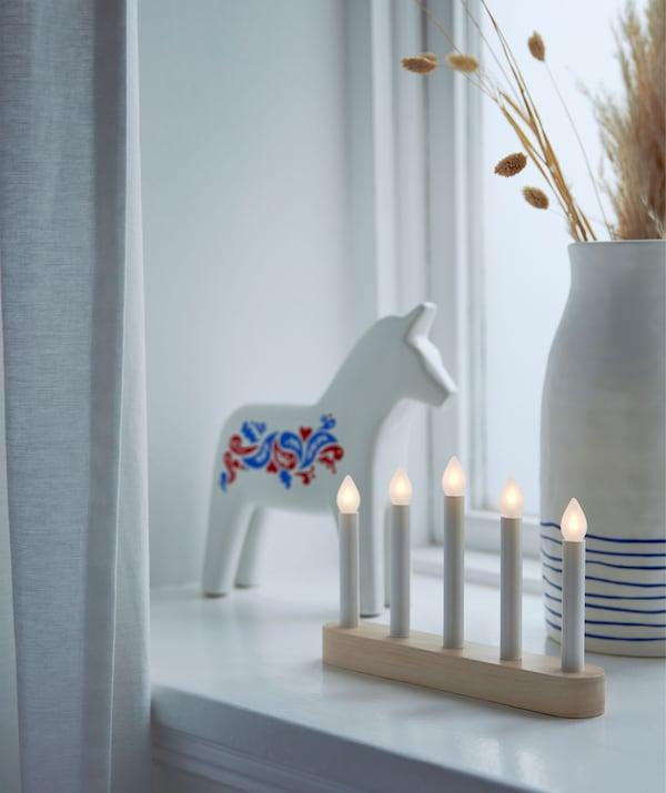 Alféizar de una ventana decorado con un caballo de madera de Dalecarlia, un candelabro LED y un jarrón de cerámica con ramas secas.