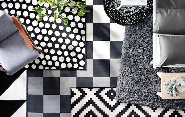 Alfombras blancas y negras de texturas y estampados diferentes superpuestas en el suelo de un salón vistas desde arriba.