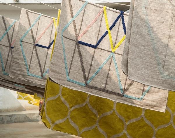 Alfombras multicolor de IKEA PS tejidas a mano colgadas al sol.