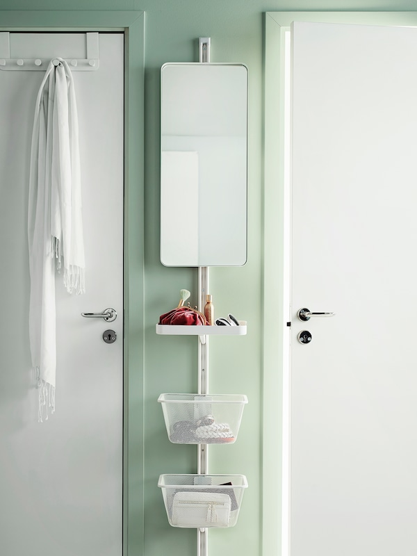 ALGOT storage mounted vertically on a narrow piece of wall between two doors. Includes a mirror, shelf and baskets.